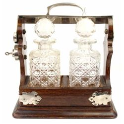 Antique double decanter tantalus set in original oak frame, original cut glass decanters and keys. D