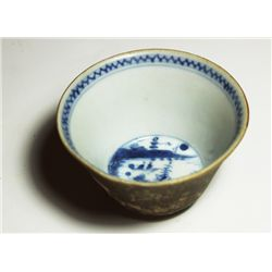 Small Chinese blue-on-white porcelain teacup, man-on-shore motif in center, brown exterior.