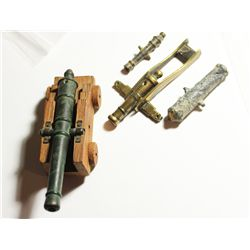 Collection of 4 miniature cannons (bronze, brass and pewter), one with wooden carriage, probably Bri