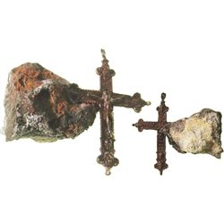 Brass cross with Jesus figure (complete) encrusted into piece of impacted debris.