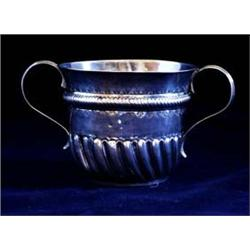A QUEEN ANNE TWO HANDLED PORRINGER with curved lobes and fluting to lower half and a gadrooned band,