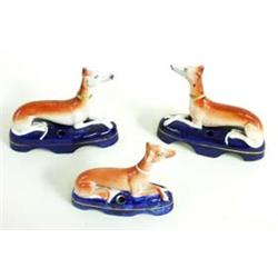 THREE 19TH CENTURY STAFFORDSHIRE INKWELLS in the form of alert recumbent greyhounds on a blue base,.