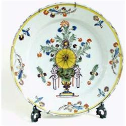AN 18TH CENTURY POLYCHROME DELFT CHARGER centred a floral display and with floral sprigs to border,.