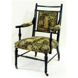 AN EBONISED EDWARDIAN ARMCHAIR with reeded crest rail and upholstered back, the part upholstered arm