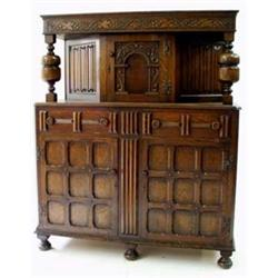 A CARVED OAK COURT CUPBOARD the top with trailing vine frieze on baluster end supports, the central.