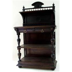 A LATE VICTORIAN DARK OAK BUFFET the back centred raised cresting with carved maskhead dividing fini