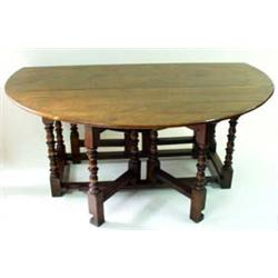 "AN 18TH CENTURY STYLE ELM DINING TABLE with ""D"" shaped drop leaves, of good honey colour, on turned."