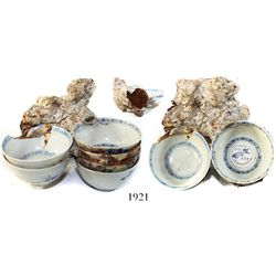 Encrusted conglomerate of 6 Chinese blue-on-white porcelain teacups and an iron object.