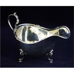A SILVER SAUCE BOAT: with tube lined and decorated rim with scroll  handle, raised three scroll a...