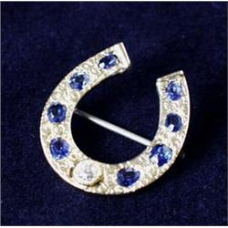 A SCROLL ENGRAVED GOLD HORSESHOE BROOCH: set a single diamond,  dividing groups of four sapphires...