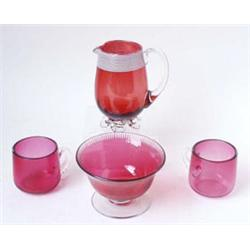 A VICTORIAN CRANBERRY GLASS CREAM JUG: with clear glass handle and  crimped clear glass feet, the...