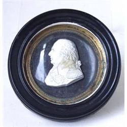 AN EARLY 19TH CENTURY MINIATURE RELIEF MALE BUST: plaster set in  convex glass, signed Desprez Ru...