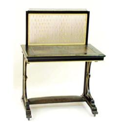 AN EDWARDIAN EBONISED WRITING TABLE: the top with moulded edge and  inset a tooled green skiver,...