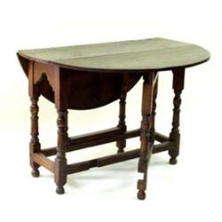 A 19TH CENTURY OAK D-END GATELEG TABLE: on baluster supports united  plain stretchers, on turned...