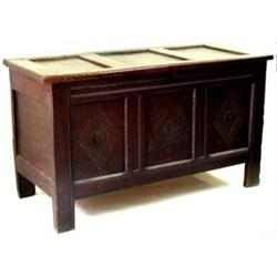AN 18TH CENTURY OAK KIST: with triple panel top, the triple panel  front carved flowerheads withi...