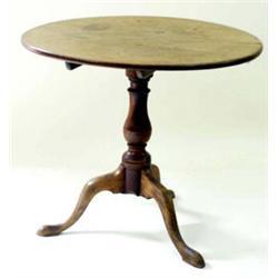 A GEORGIAN MAHOGANY TILT TOP TABLE: the circular top on turned pillar  support, the three splay l...