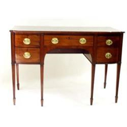 A EARLY 19TH CENTURY MAHOGANY SIDEBOARD: the top shaped to front,  over a central long drawer div...