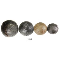 Lot of four small to medium-sized iron cannonballs.