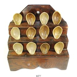 Lot of 12 Chinese porcelain spoons in a wooden display rack.