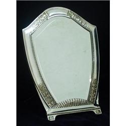 A HANDSOME SILVER PLATED SHIELD SHAPED EASEL MIRROR: the plate  bevelled, the frame with foliate