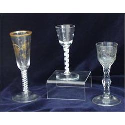 AN EARLY 19TH CENTURY WINE GLASS: with ogee bowl, wheel cut roses and  hexagonal facet cut, on fa