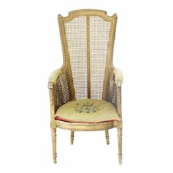 A 19TH CENTURY BERGERE STYLE ARMCHAIR: with scrolled padded arms,  raised circular tapering stop