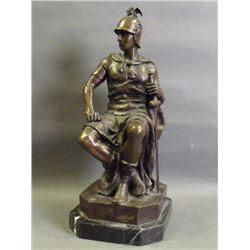 A bronze figure of a seated warrior with sword by
