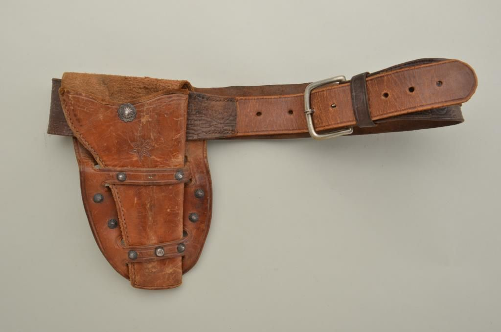 Antique holster and belt rig in Western style showing wide skirt for  holster and decorated with old