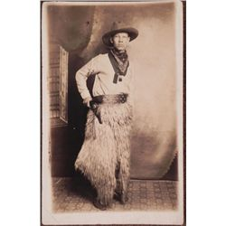 VINTAGE PHOTO POSTCARD OF COWBOY WITH SIX-GUN AND CHAPS