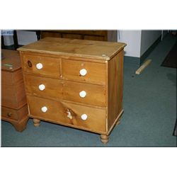 An antique four drawer pine bedroom chest with porcelain knobs
