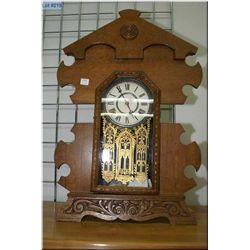 A vintage oak Gingerbread clock with decorative cast pendulum,  gilt litho glazed door, in  excellen