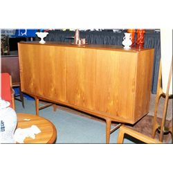 A teak four door sideboard with on fitted drawer section