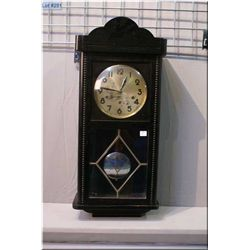 A vintage wall clock with visible pendulum
