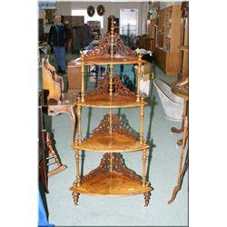 A four tier Victorian burl walnut étagère with fretwork backs and porcelain castors