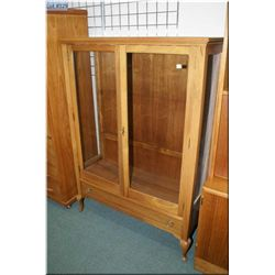 A semi-contemporary maple two door display cabinet with cabriole feet