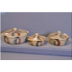 Three lidded Medalta casserole dishes in graduated sizes