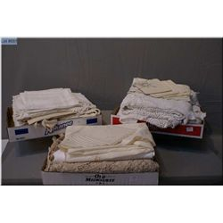 A selection of vintage table linens including large cotton, damask and lace clothes and matching nap