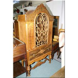 An antique single door, single drawer curved top china cabinet