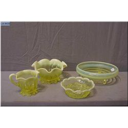 Four pieces of canary yellow and opalescent uranium glass including cream and sugar, small  candy di