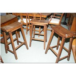 Three saddle style walnut bar stools