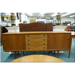 """A  mid century modern teak sideboard 72"""" wide with four drawer center section and sliding doors on e"""