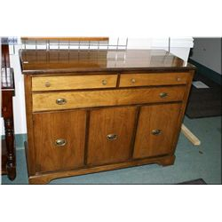 A mid 20th century sideboard with three doors and three drawers