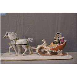 A German Dresden figurine featuring sleigh riders and horses