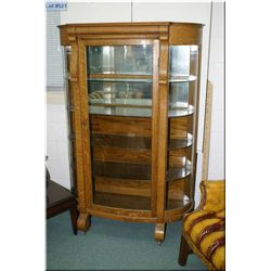 An antique quarter cut oak Empire style curved glass display cabinet