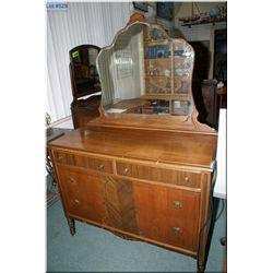 A walnut four drawer dresser with bevelled mirror