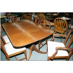 A Deco era double pedestal walnut dining table with two jack knife leaves and six chairs
