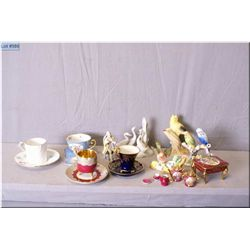 A selection of collectibles including Limoges  miniatures, German figurine, four small cups and  sau