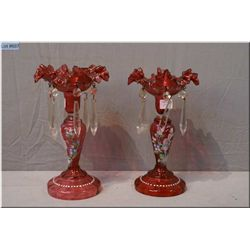 A pair of matching cranberry glass Mary Gregory style candlesticks with hanging lustres