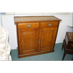 A two door, two drawer cabinet with original finish and hardware