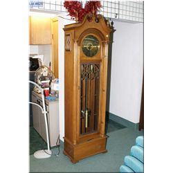A modern walnut  triple train long case clock with German movement